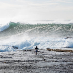 Surf's Up - a lone surfer watching a massive wave roll in