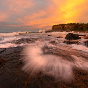 Fire Spray - Sunset lights up the endless movement of water on the Kiama Coast Walk, Australia