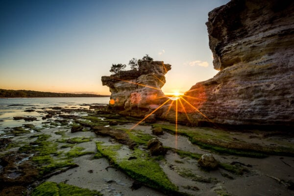 A dramatic sunset through the Hole in the Wall. Booderee National Park, Australia